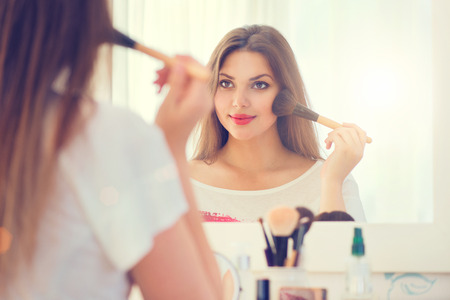 woman mirror: Beauty woman looking in the mirror and applying makeup Stock Photo