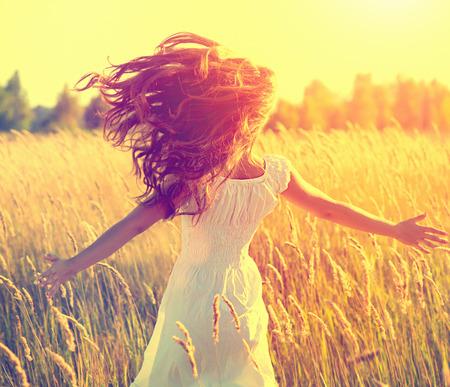 Piękna dziewczyna z długimi zdrowe włosy dmuchanie działa na polu Zdjęcie Seryjne