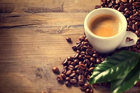 frijoles: Taza de café en el fondo de madera decorada con granos de café