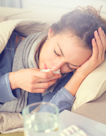 flue season: Flu. Woman caught cold. Sneezing into tissue