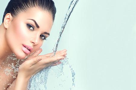 Mooie model vrouw met spatten van water in haar handen Stockfoto