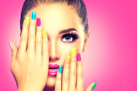 mode: Skönhet flicka ansikte med färgrik nagellack Stockfoto