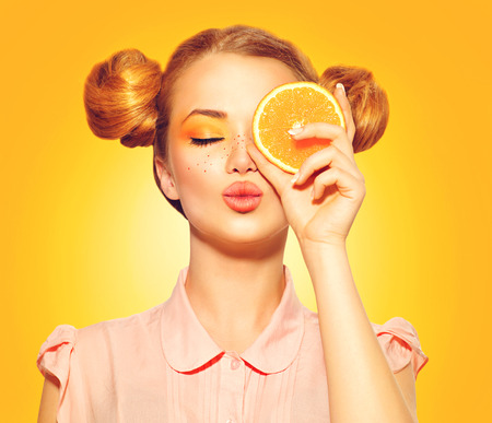 orange slices: Beauty model girl takes juicy oranges