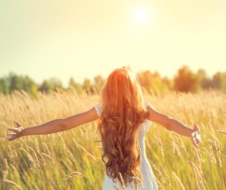 ao ar livre: Menina da beleza com cabelos longos desfrutar da natureza, levantando as mãos