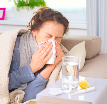 Sick woman sneezing into tissue. Flu. Woman caught cold