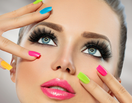 bright: Beauty girl face with colorful nail polish. Manicure and makeup Stock Photo