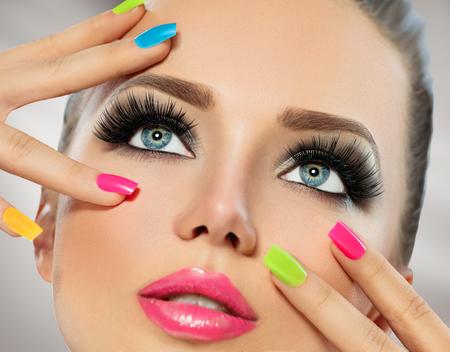 Pielęgnacja twarzy dziewczyna z kolorowych paznokci. Manicure i makijaż