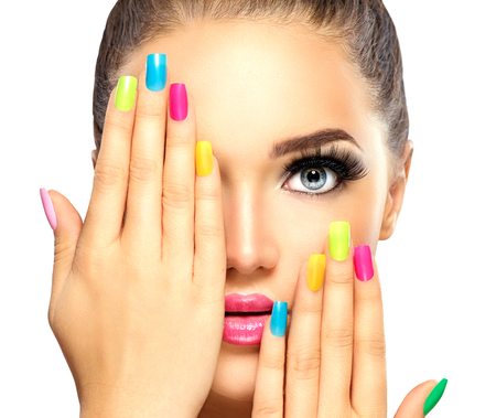 Beauty girl face with colorful nail polish. Manicure and makeup Imagens