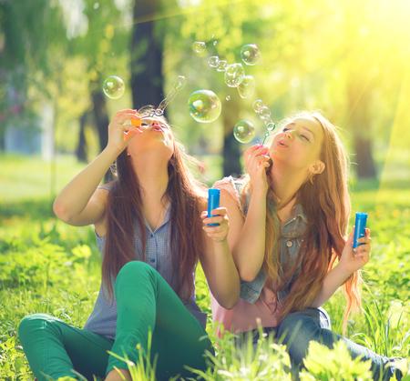 jovenes estudiantes: niñas adolescentes de la belleza que soplan burbujas de jabón en el parque de la primavera