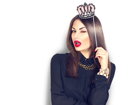 Knipogende sexy model meisje met grappige papieren kroon op stok