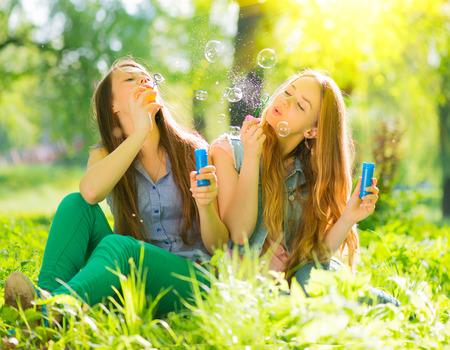 Beauty teen girls reading magazine and having fun outdoors