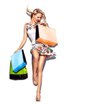 Mulher da beleza com sacos de compras em vestido branco curto. Compras