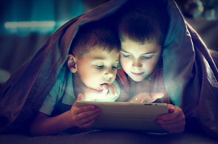 밤에 담요에서 태블릿 PC를 사용하여 두 아이 스톡 콘텐츠