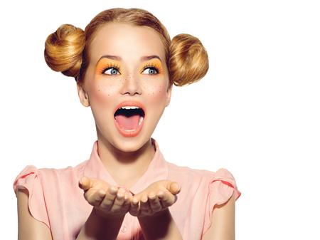 La muchacha alegre adolescente con pecas, peinado y maquillaje divertido rojo amarillo Foto de archivo