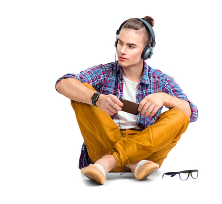 젊은 패션 남자 바닥에 앉아 음악을 즐기는