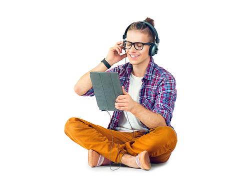 Jonge mode man op de grond zitten en genieten van muziek