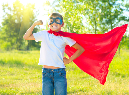 strong: Superhero kid showing his muscles over nature background Stock Photo