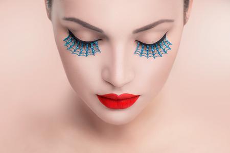 Cara de la belleza de la moda modelo de la mujer. Retrato con los labios atractivos rojos y pestañas postizas azules Foto de archivo