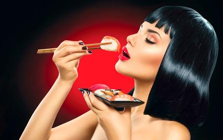 Sushi. Fashion art portrait of beauty model girl eating sushi