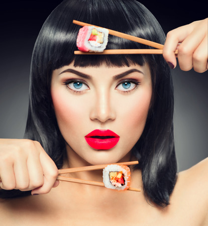 Sushi. Fashion art portrait of beauty model girl eating sushi rolls Stok Fotoğraf