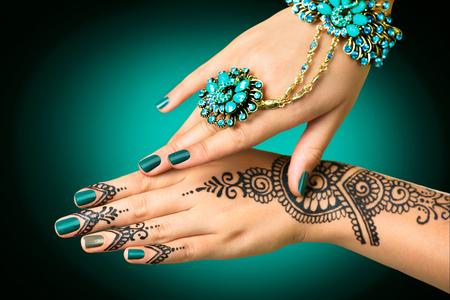 Manos de la mujer con el tatuaje del mehndi. Manos de la chica novia india con tatuajes de henna negro Foto de archivo