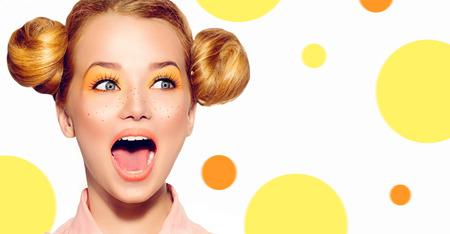 skönhet: Joyful tonåring flicka med fräknar, rolig röd frisyr och gul smink