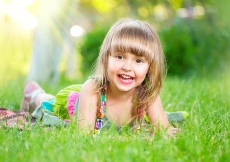 only girls: Portrait of a smiling little girl lying on green grass