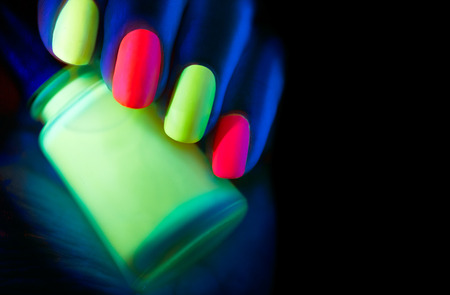 nailart: Fluorescent nail polish. Fashion model woman nails in neon light