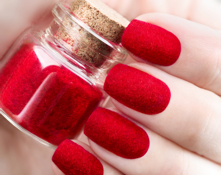 Velvet nails. Fashion trendy red fluffy nailart design closeup