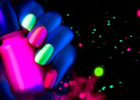 형광 매니큐어. 네온 불빛에 패션 모델 여자 손톱