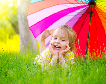 Portrait of a smiling little girl lying on green grass under the colorful umbrella