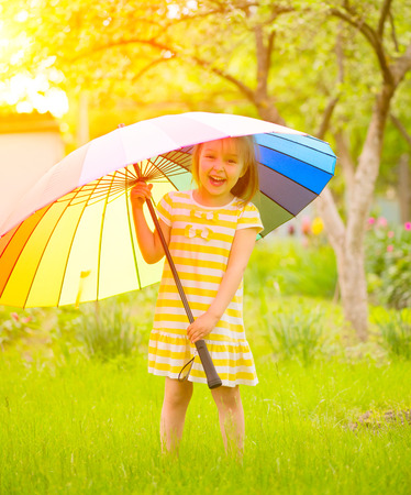 staying: Smiling little girl staying on green grass under the colorful umbrella