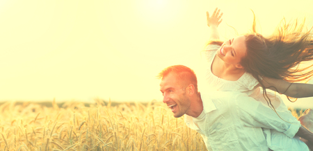Happy couple having fun outdoors on wheat field over sunset 스톡 콘텐츠