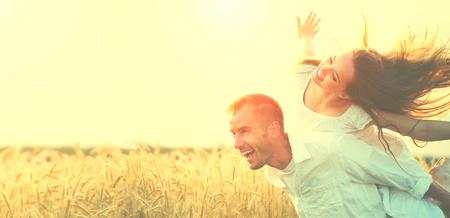 Gelukkig paar dat pret in openlucht op tarwe veld over zonsondergang Stockfoto
