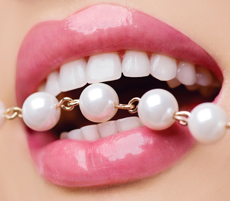 pearly: Woman smiles showing white teeth, holding a pearly necklace into the mouth