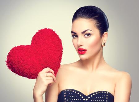 femme brune sexy: Sexy femme brune tenant en forme de coeur oreiller rouge