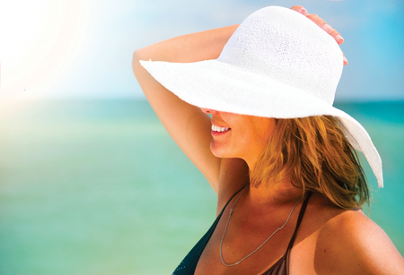 Woman in a big white hat tanning on the beach. Summer holidays, vacation concept