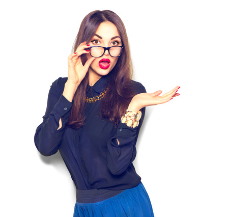 space for text: Surprised girl wearing glasses and showing empty copy space on open hand palm for text Stock Photo