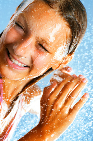 shower water: Happy teenage girl taking a shower. Water drops Stock Photo
