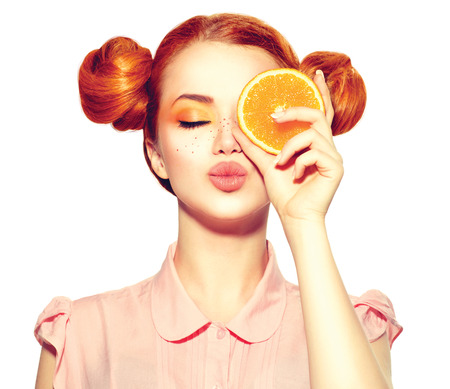 時尚: 美麗快樂的年輕女孩,持有多汁的橙片雀斑