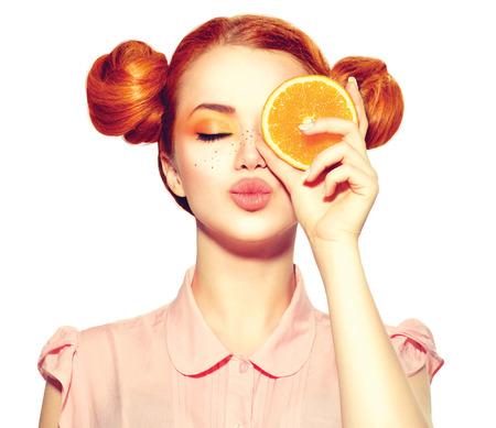 Menina adolescente alegre bonita com sardas segurando uma fatia de laranja suculenta