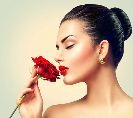 Fashion brunette model girl face portrait with red rose in her hand Foto de archivo