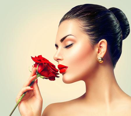 Fashion brunette model meisje gezicht portret met rode roos in haar hand