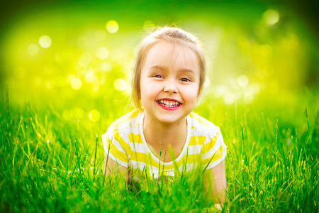 1: Portrait of a smiling little girl lying on green grass