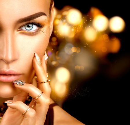 oro: moda mujer de belleza con maquillaje de oro, accesorios y uñas