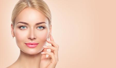 femme de beauté visage closeup portrait. Spa fille toucher son visage Banque d'images
