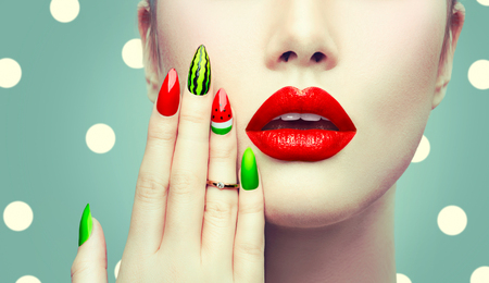 red lip: Watermelon nail art and makeup closeup over polka dots background Stock Photo