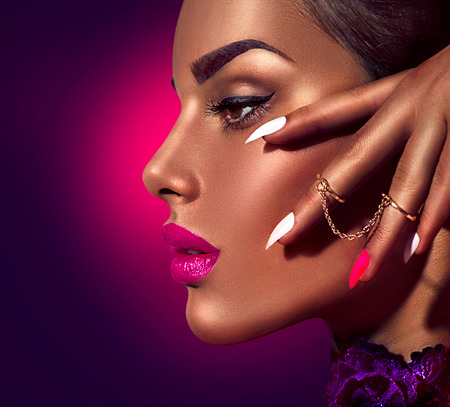 Sexy model with brown skin and purple lips over dark background Stock Photo