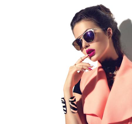 menina modelo da forma da beleza com o cabelo castanho usando óculos de sol à moda