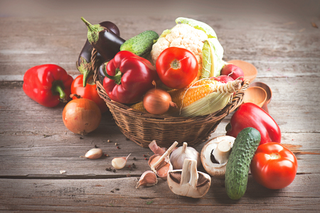 Healthy organic vegetables in basket on wooden background Stock Photo